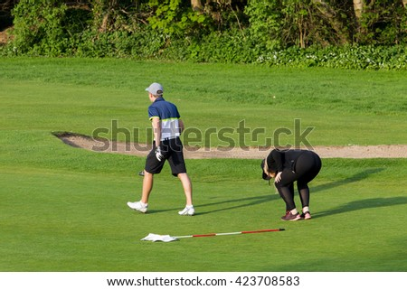 Couple playing golf on green.  Blonde woman bending over to get ball