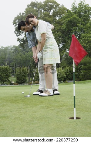 Couple playing golf together - stock photo