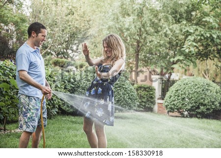 Couple playing in garden with water hose  - stock photo