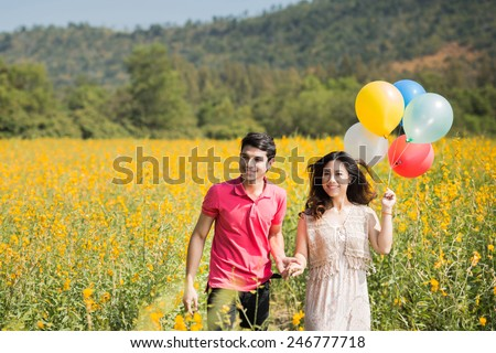 Couple playing in the garden flowers yellow balloons. Both happy and smiling on Valentine's Day - stock photo