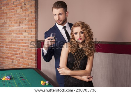 Couple playing roulette at casino - stock photo