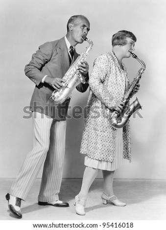 Couple playing saxophones together - stock photo