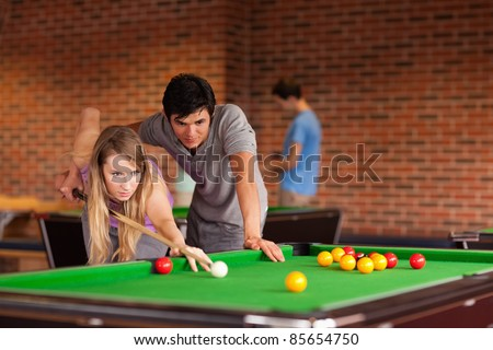 Couple playing snooker in a student home - stock photo