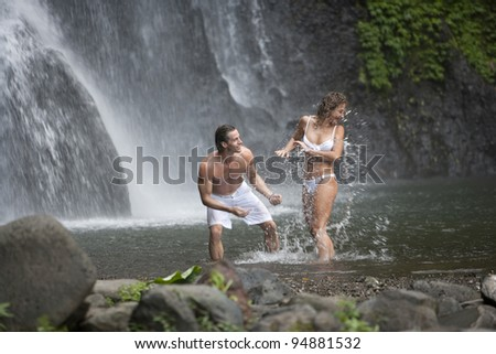 Couple playing under waterfalls.