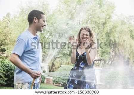 Couple playing with a garden hose and spraying each other