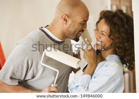 Couple playing with paint rollers - stock photo