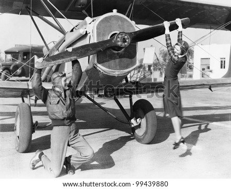 Couple playing with propeller on plane - stock photo