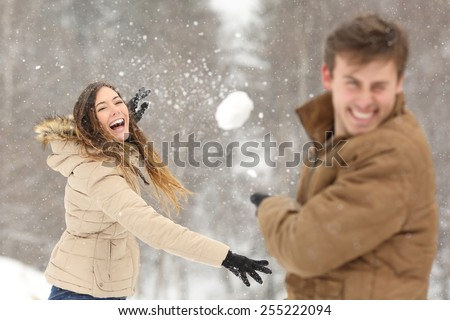 Couple playing with snow and girlfriend throwing a ball in winter holidays - stock photo