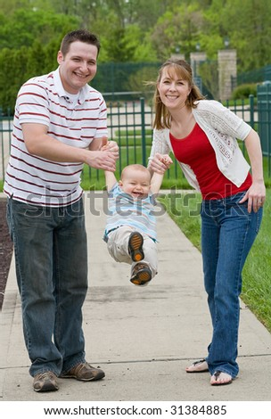 Couple Playing With Their Son - stock photo