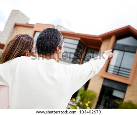 Couple pointing at their lovely dream home - stock photo