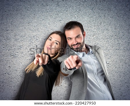 Couple pointing to the front over textured background  - stock photo