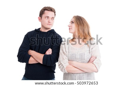 Couple posing and standing with arms crossed and looking at each other isolated on white background