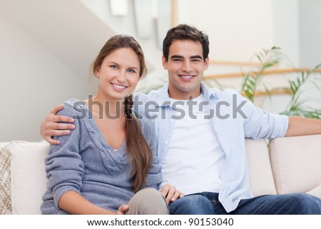 Couple posing in their living room while looking at the camera
