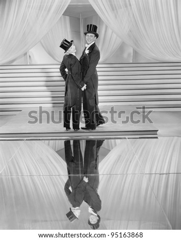 Couple posing in tuxedos and reflection - stock photo