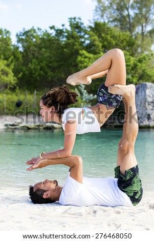 Couple practicing acroyoga at sunrise - stock photo