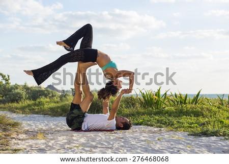 Couple practicing acroyoga at sunrise - stock photo