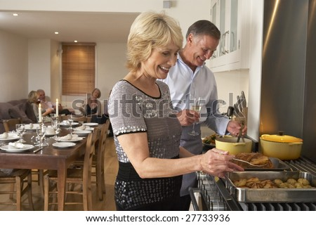 Couple Preparing Food For A Dinner Party
