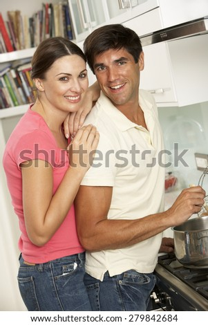 Couple Preparing Meal At Cooker