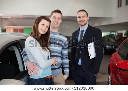 Couple purchasing a car in a dealership - stock photo