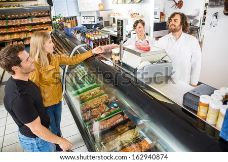 Couple purchasing meat from salesman at counter in butcher's shop - stock photo