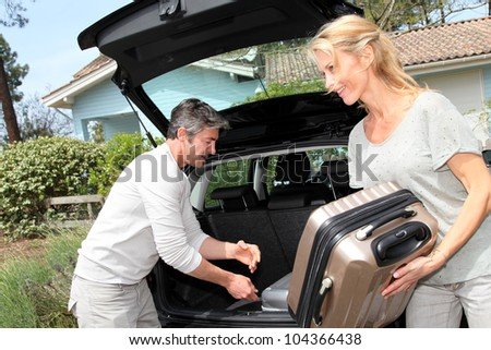 Couple putting suitcases in car trunk for a journey - stock photo