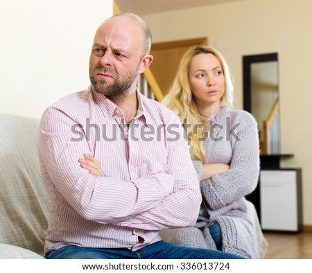 Couple quarrel. Sad man and girl during quarrel  in living room at home