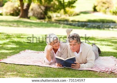Couple reading a book in the park - stock photo