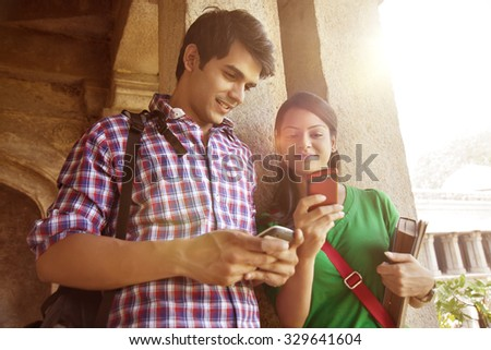 Couple reading an sms on a mobile phone - stock photo