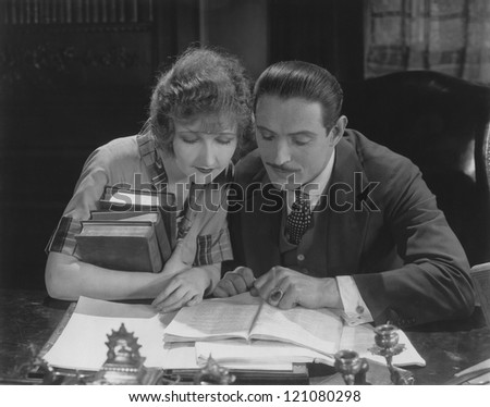 Couple reading book at desk - stock photo