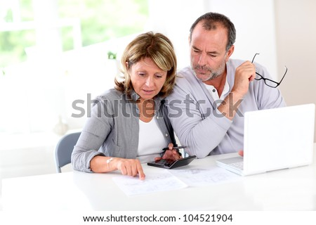 Couple reading construction plan at home with use of laptop - stock photo