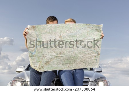 Couple reading map while leaning on car hood during road trip - stock photo