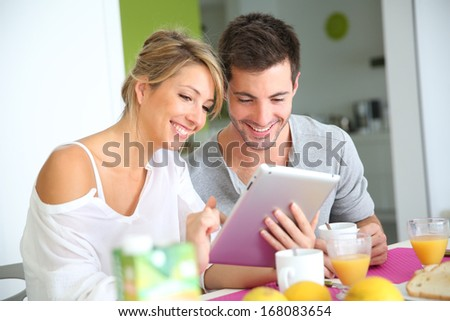 Couple reading news on digital tablet - stock photo