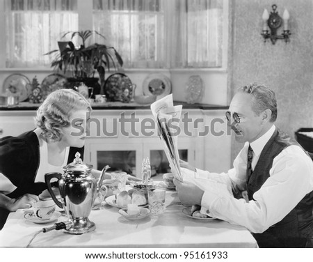 Couple reading newspaper at breakfast table
