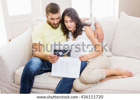 Couple reading newspaper in living room at home