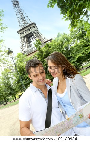 Couple reading tourist map in front of the Eiffel tower - stock photo