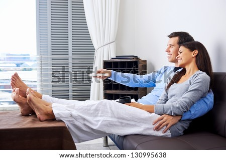 couple reaxing watching tv at home on the couch with embrace and cuddle - stock photo