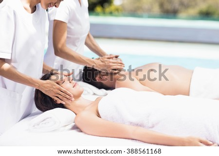 Couple receiving a face massage from masseur in a spa - stock photo