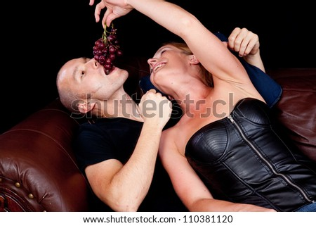 Couple reclining on a couch together, she is feeding him grapes by dangling them for him to bite - stock photo
