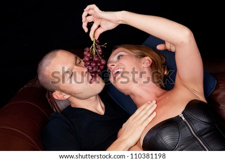 Couple reclining on a couch together, she is feeding him grapes by danling them for him to bite