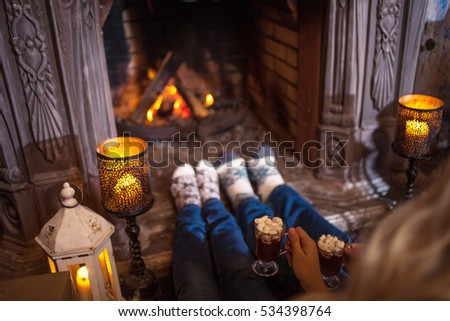 Couple relaxing at home. Feet in wool socks near fireplace. Winter holiday concept