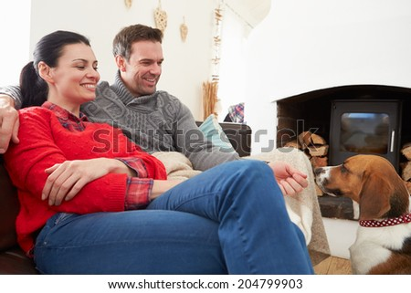 Couple Relaxing At Home With Pet Dog