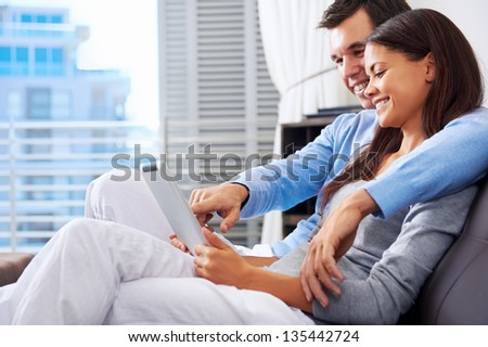 couple relaxing at home with tablet computers reading in the living room on the sofa couch. - stock photo