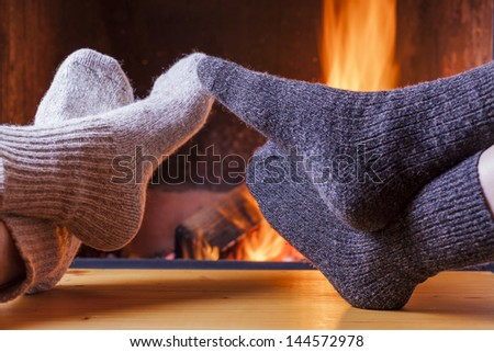 couple relaxing at the fireplace on winter evening - stock photo
