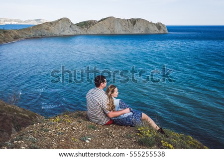 Couple relaxing by the sea with amazing mountain view. Jeans jacket, blue dress, casual style
