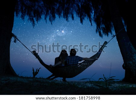 Couple relaxing in a hammock and enjoying starry sky - stock photo