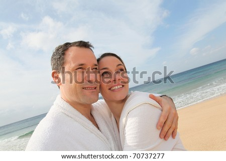 Couple relaxing in bathrobe at the beach