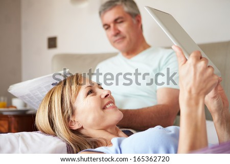 Couple Relaxing In Bed With Newspaper And Digital Tablet - stock photo