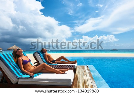 Couple relaxing in chaise lounge at the poolside - stock photo