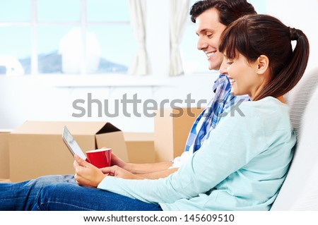 couple relaxing in new home with tablet computer on sofa couch - stock photo