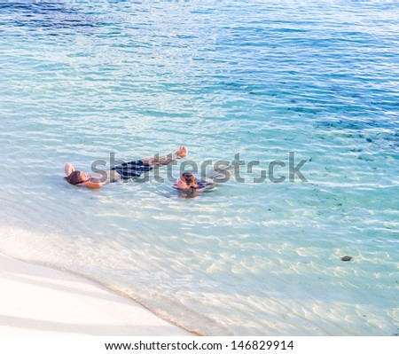 Couple relaxing in tropical waters - stock photo